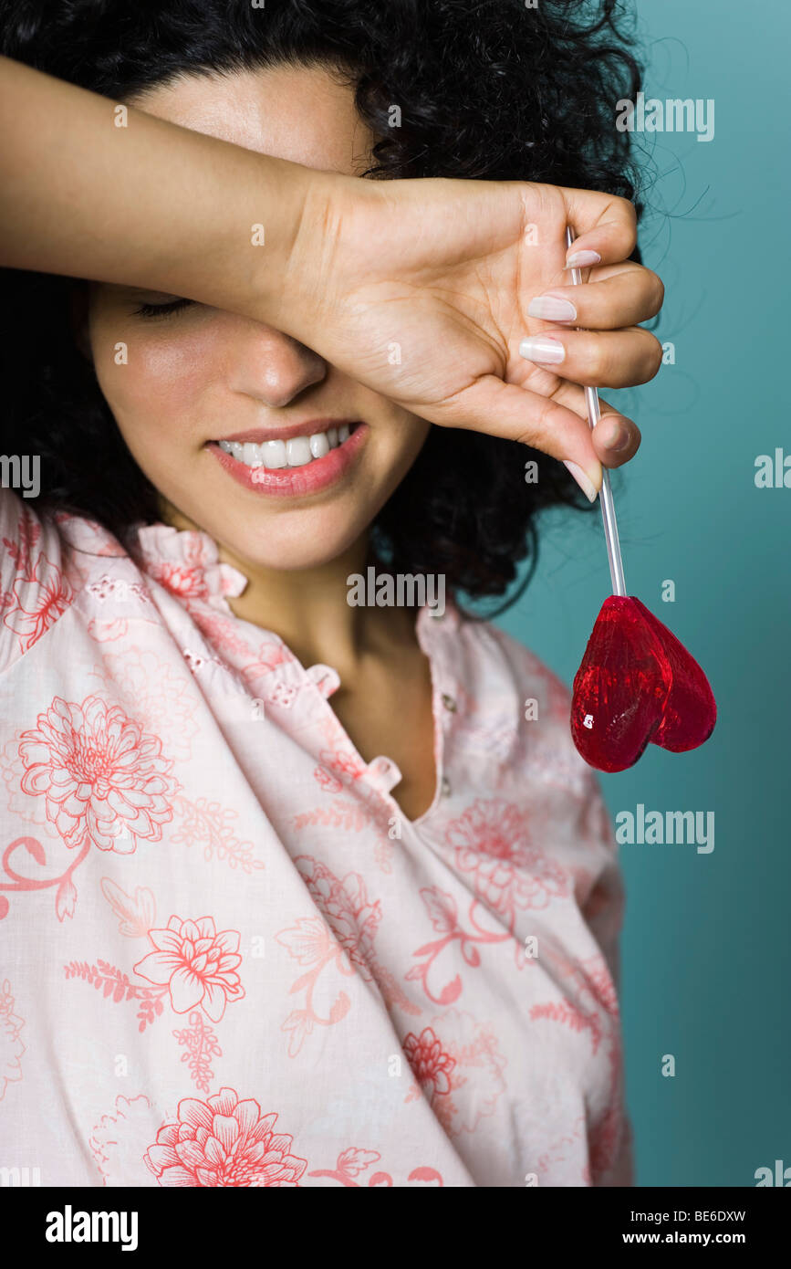 Woman smiling, covering eyes with arm, holding heart-shaped lollipop - Stock Image