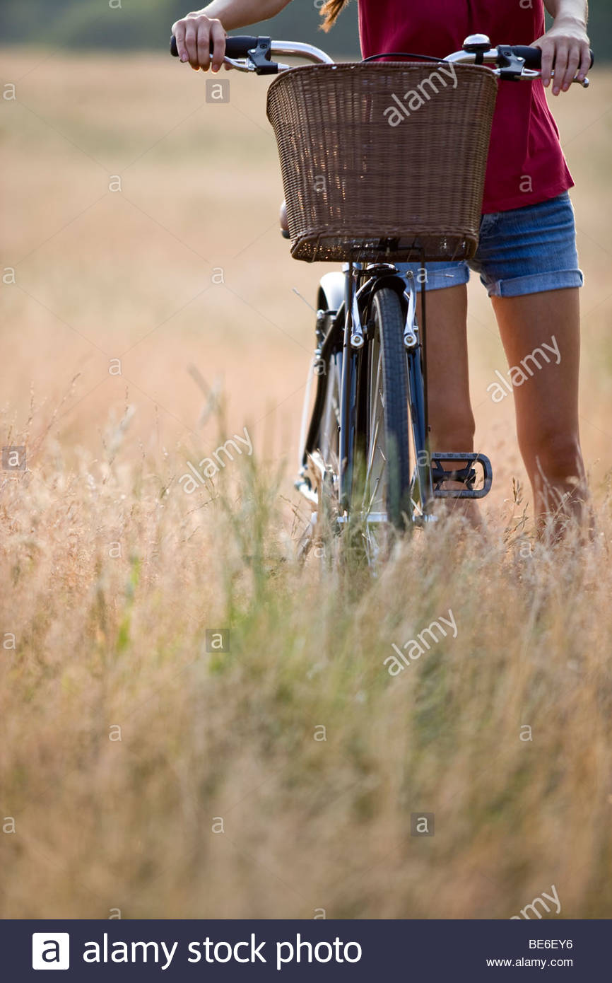A young woman pushing a bicycle through long grass - Stock Image
