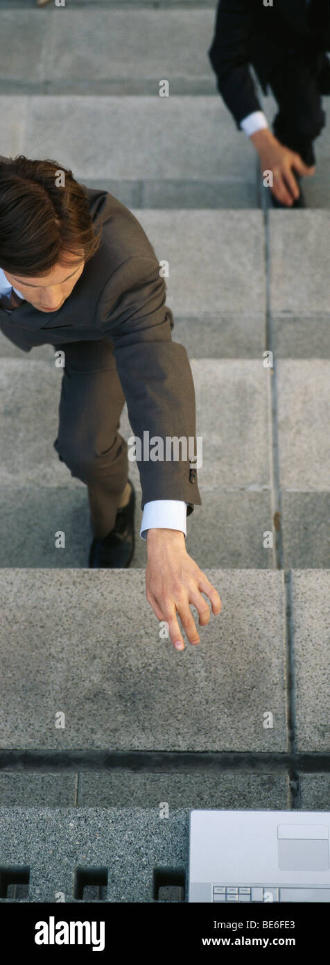 Businessmen crouching on steps reaching for laptop computer set at top of stairs - Stock Image