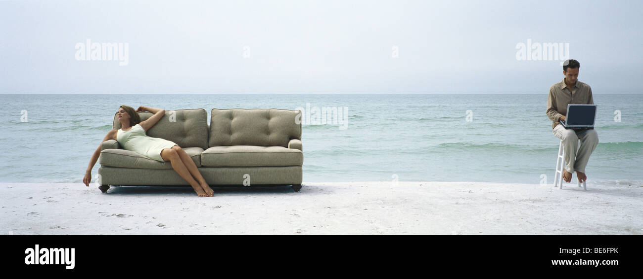 Woman reclining on sofa on beach, man on stool using laptop computer nearby - Stock Image