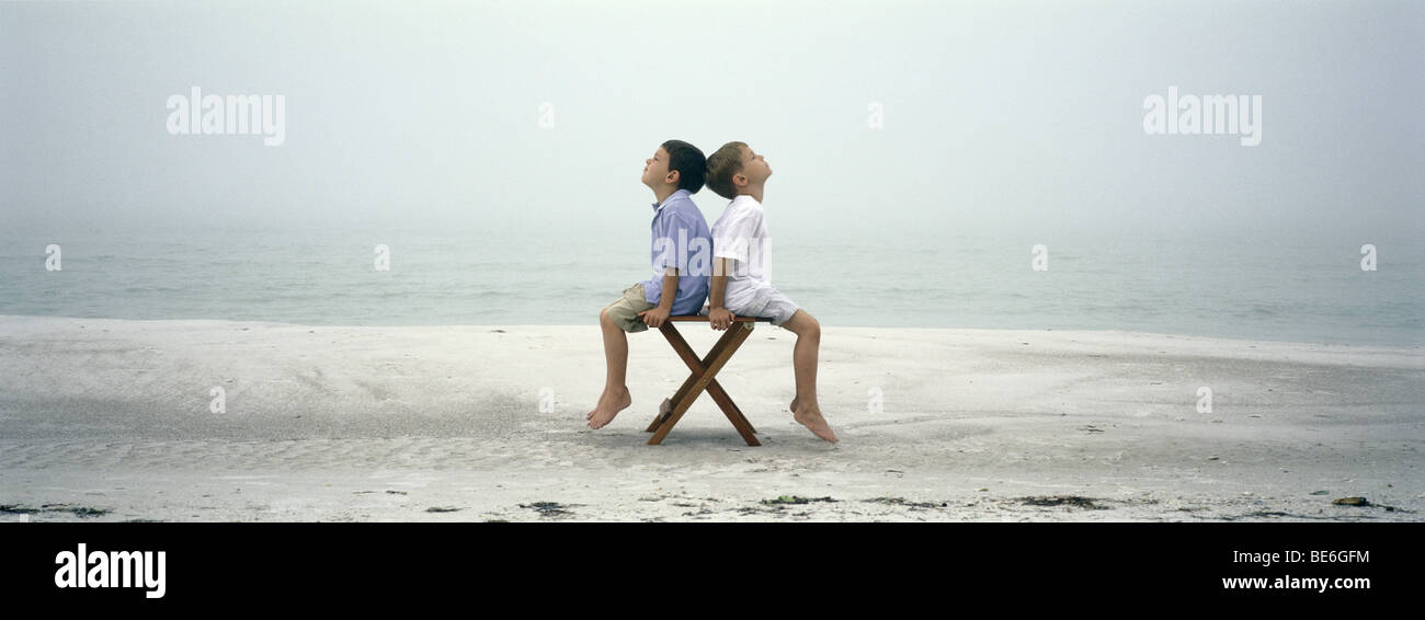 Two boys sitting back to back on chair on beach - Stock Image