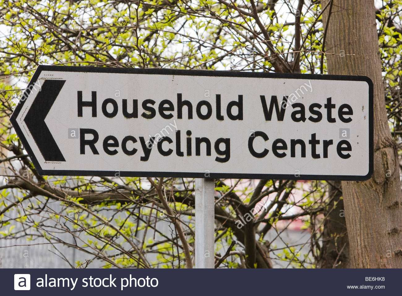 Black on white sign pointing towards a Household Waste Recycling Centre, with a tree in the background. - Stock Image
