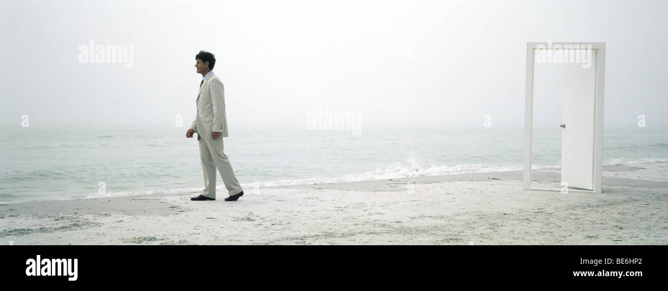 Man walking hesitantly along beach, open doorway in background - Stock Image