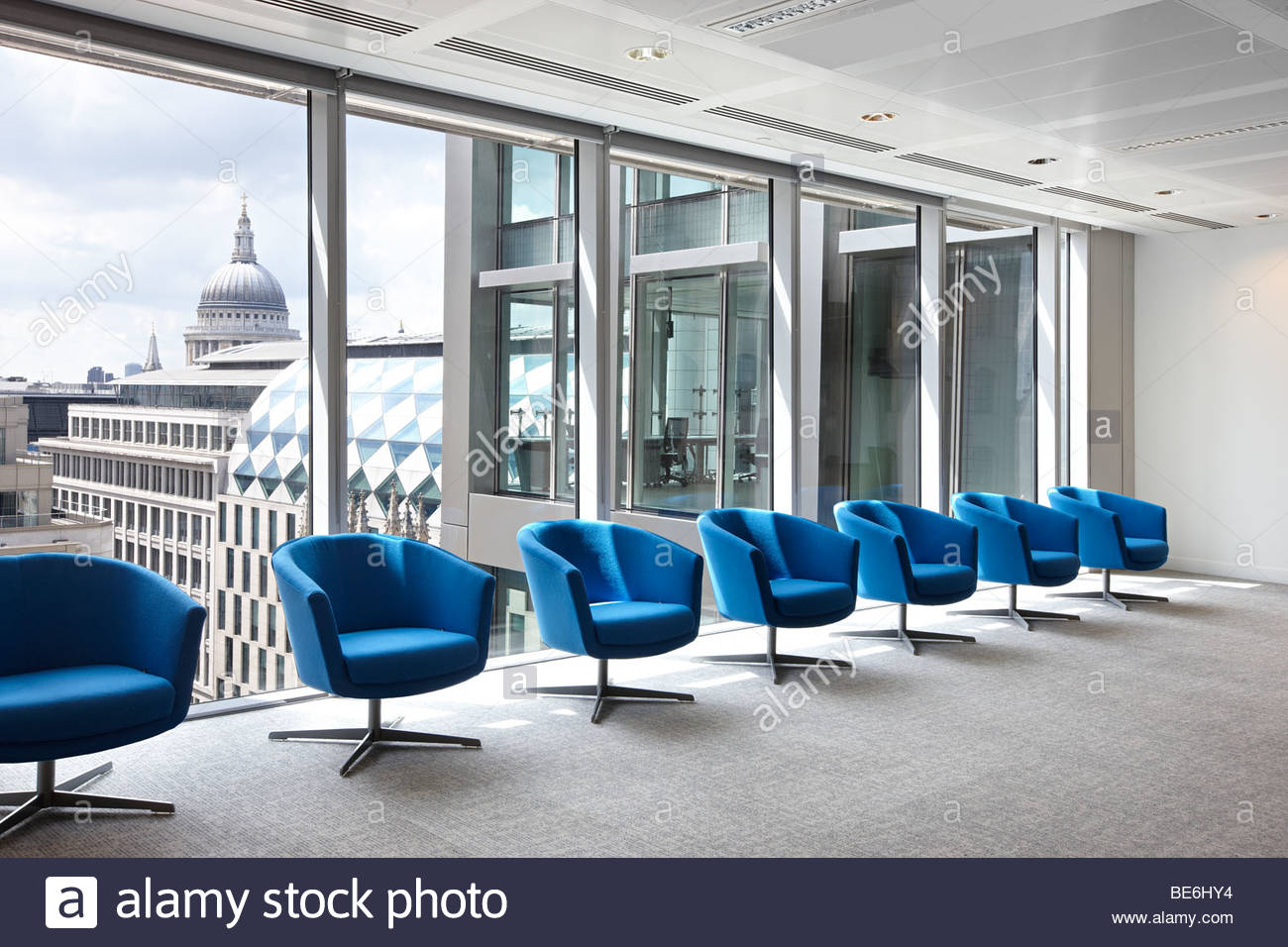 7 turquoise waiting room chairs office London - Stock Image