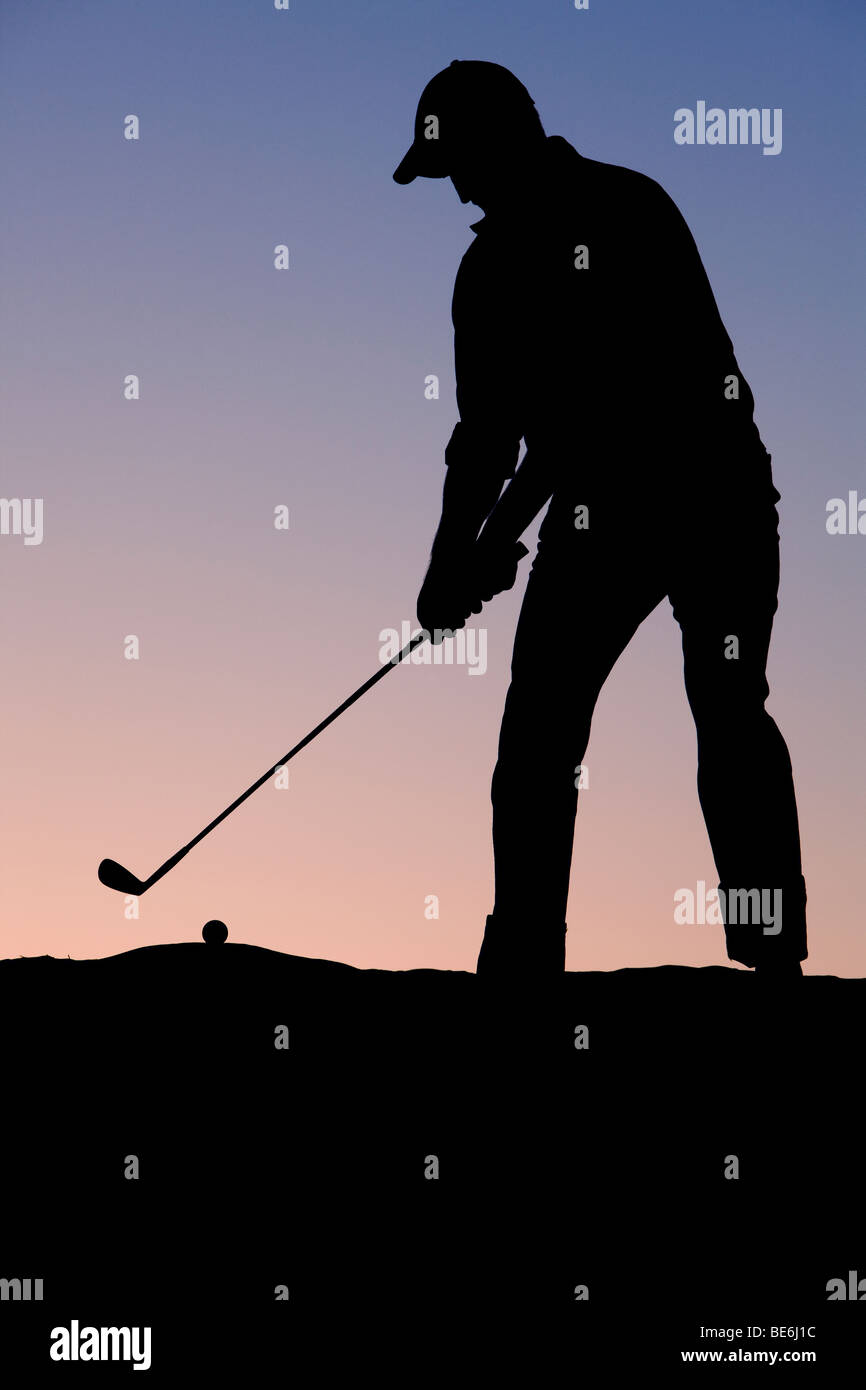 Golfer teeing off early in the morning - Stock Image