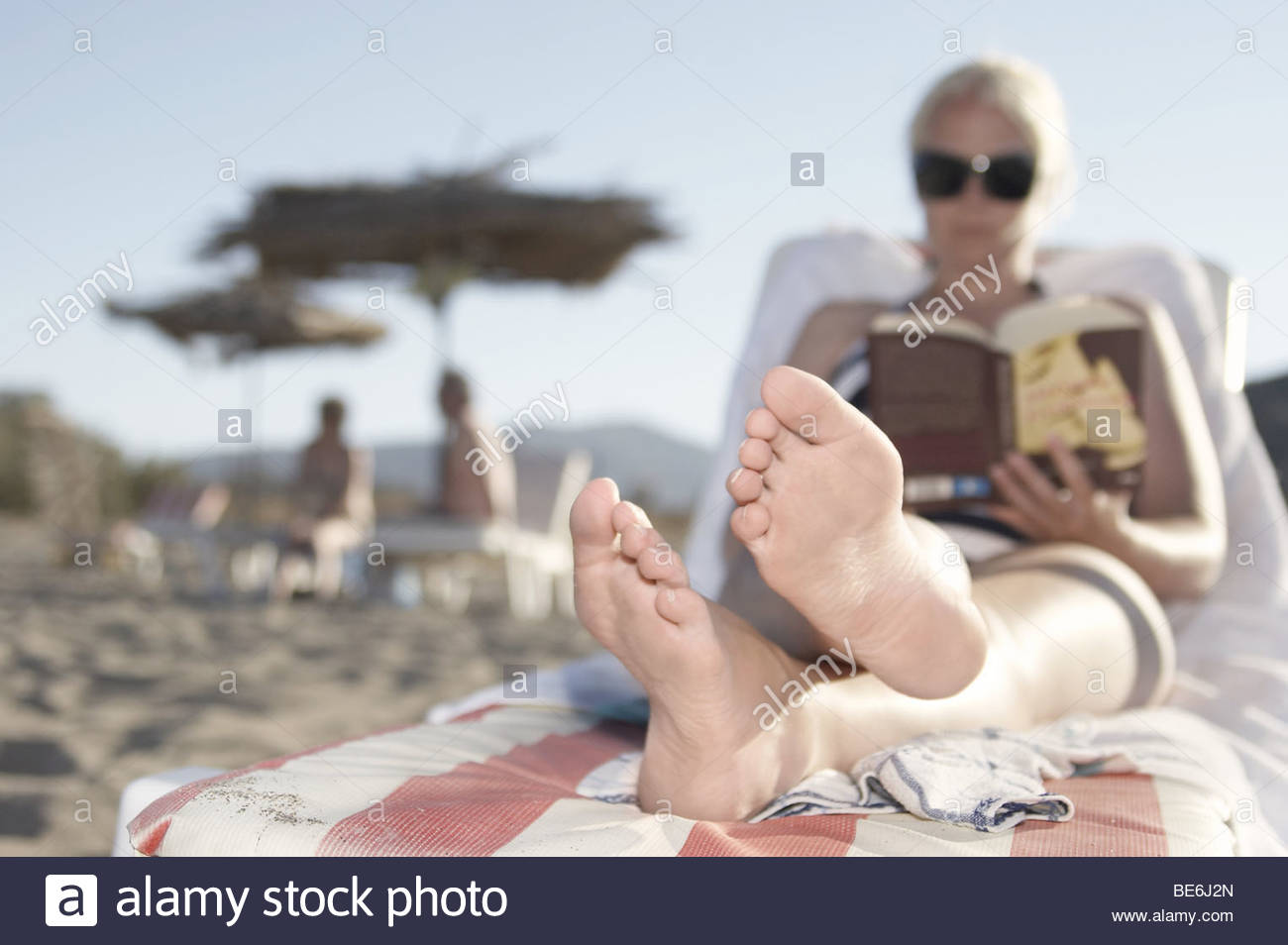 Greece   Young Woman Reclining On A Lounge Chair On The Beach And Reading A  Book
