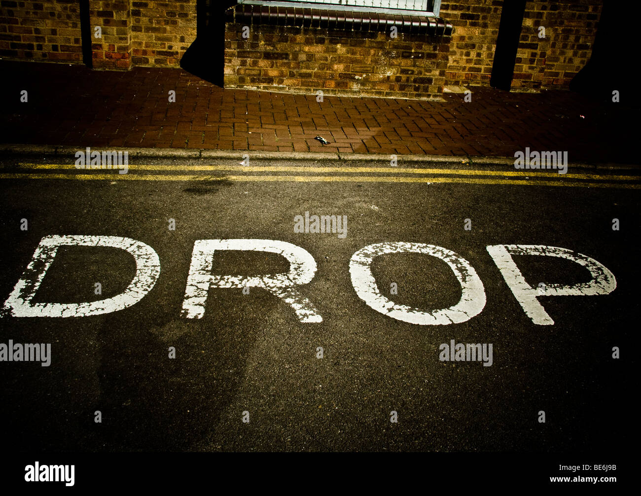 Drop written in paint on the road. - Stock Image
