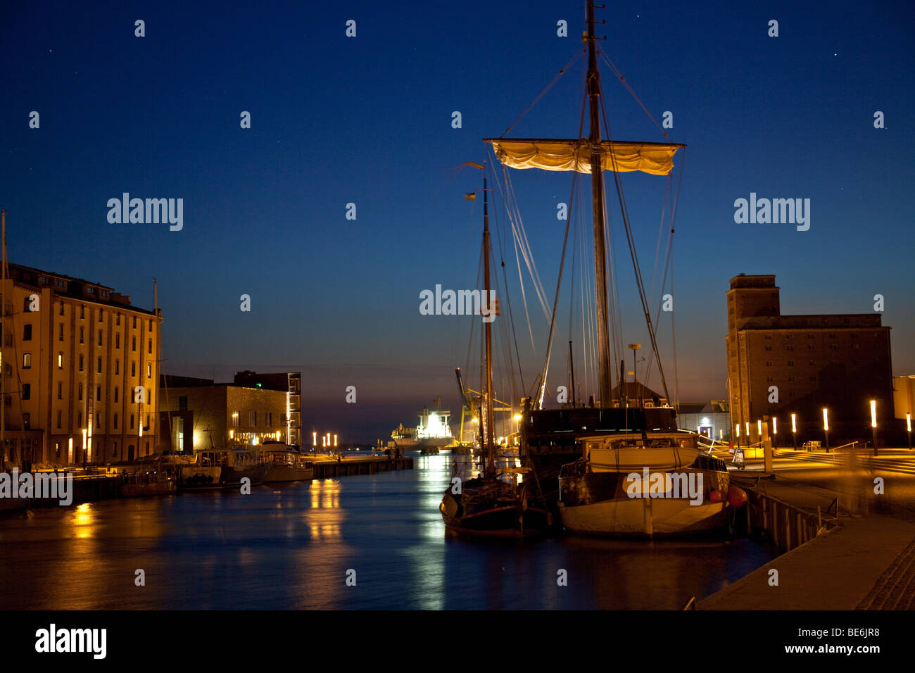 Old harbor of Wismar, Germany, with sailing boat and storehouse by night - Stock Image