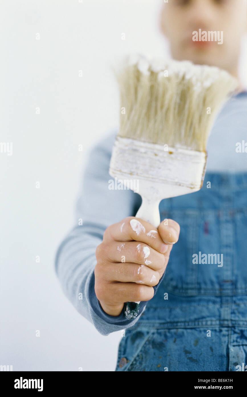 Man holding up paintbrush - Stock Image