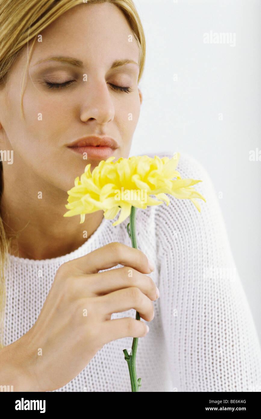 Woman enjoying flower's fragrance - Stock Image