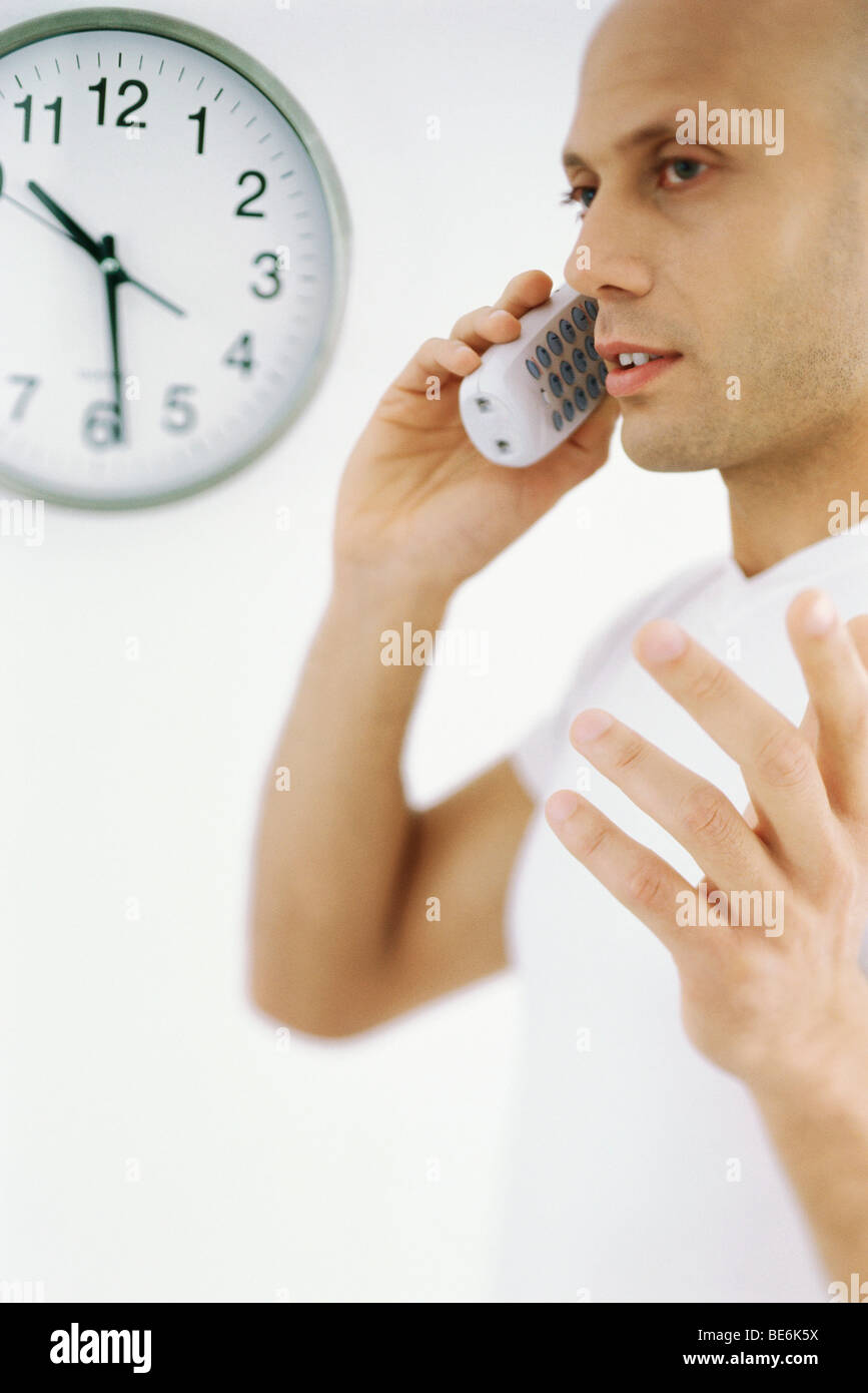 Man on phone call, clock in background Stock Photo