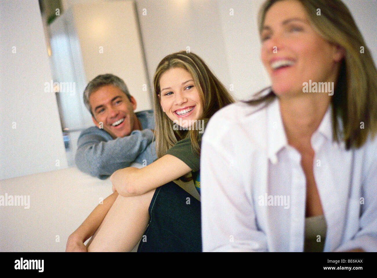 Teenage girl sitting with parents, all smiling, mother laughing - Stock Image