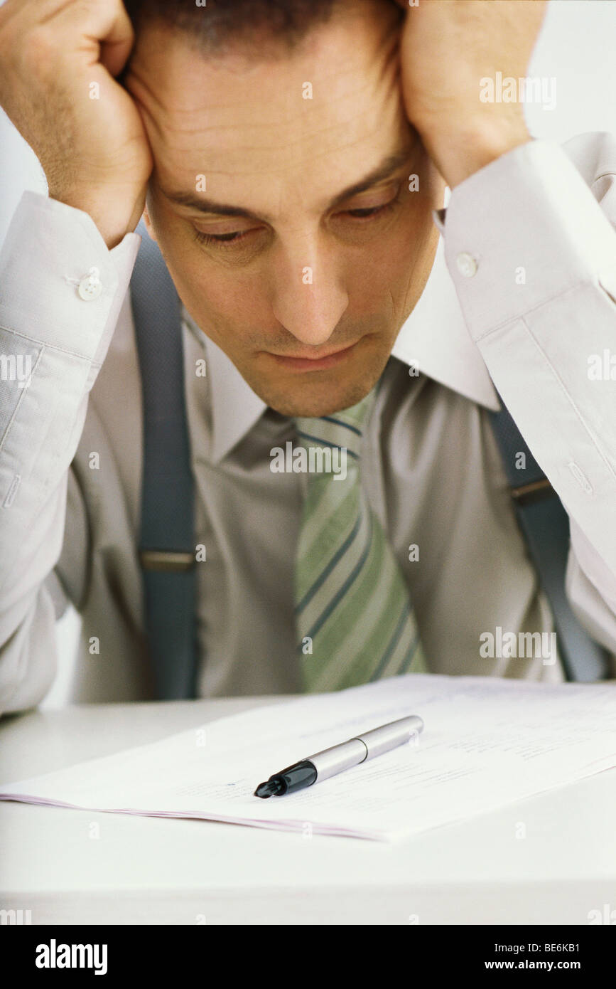 Man holding head, staring at document - Stock Image