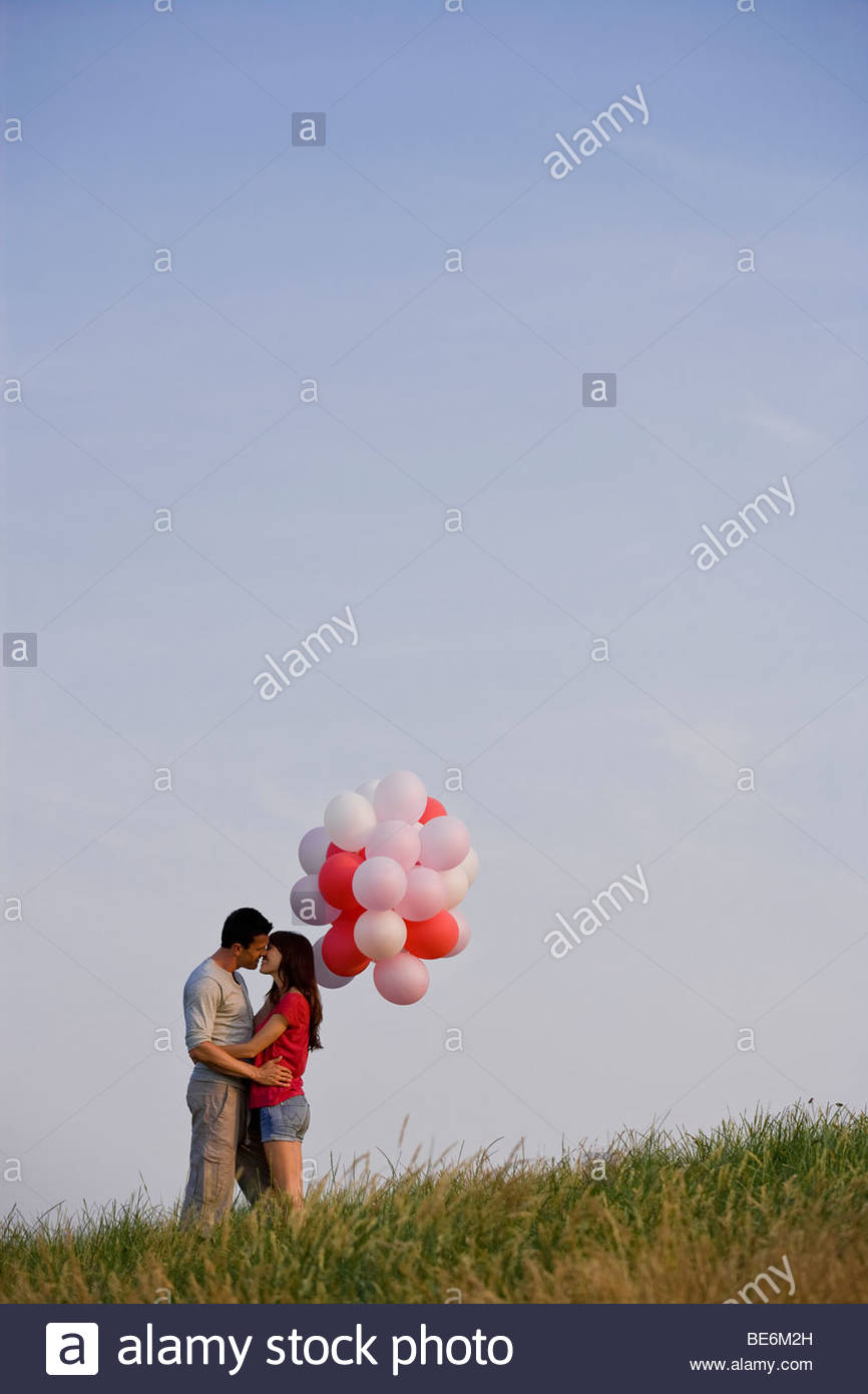 A young couple kissing, holding a bunch of red balloons - Stock Image