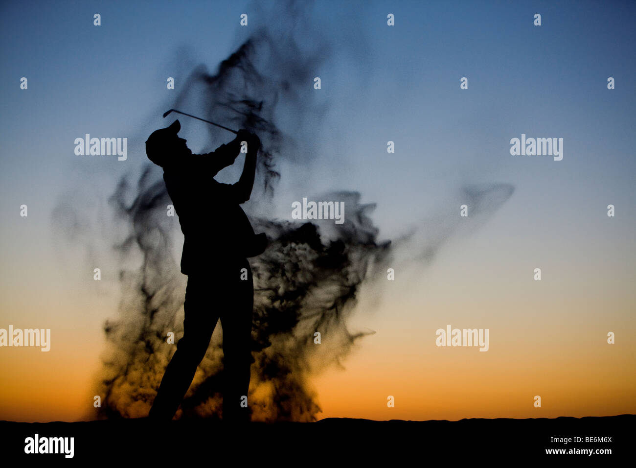 Silhouette of a golfer late in the day as he swings through a sand trap - Stock Image