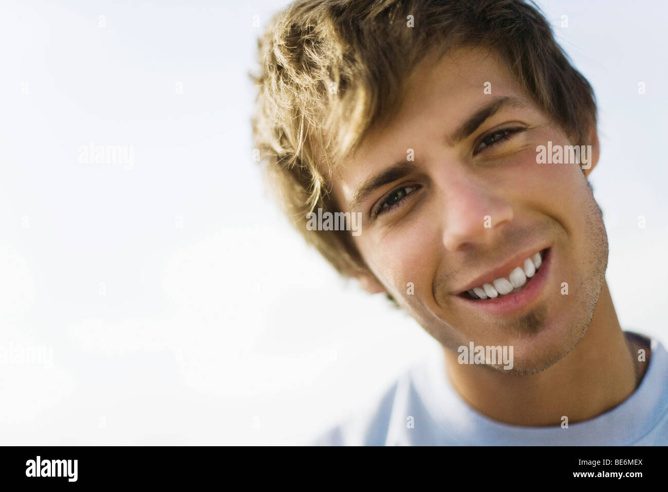 Young man smiling at camera with head tilted, portrait - Stock Image