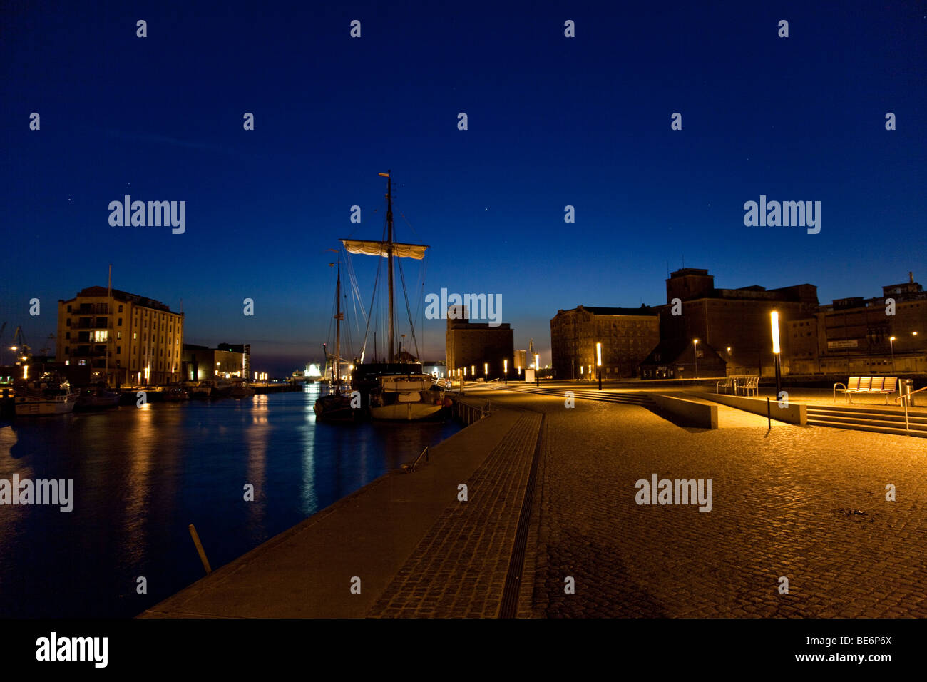 Old harbor of Wismar, Germany, with sailing boats and storehouse by night - Stock Image