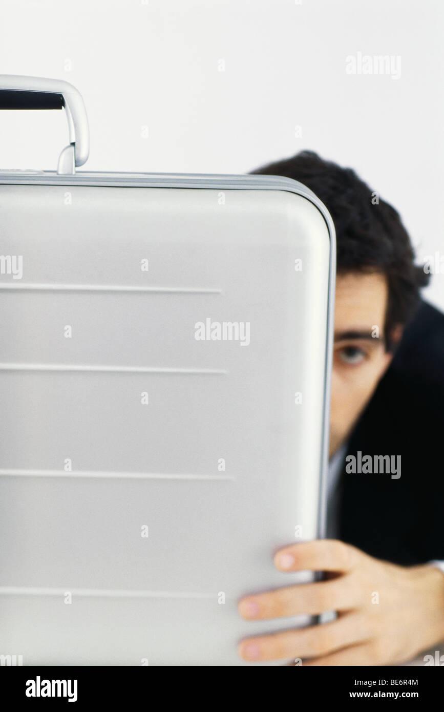 Businessman hiding behind briefcase - Stock Image