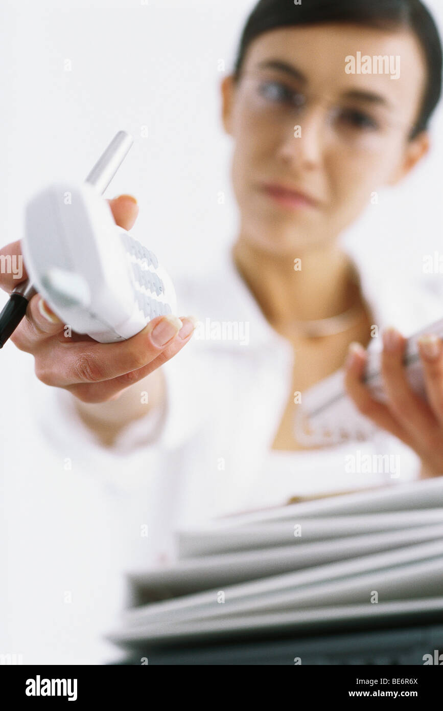 Woman holding out cordless phone, personal perspective - Stock Image