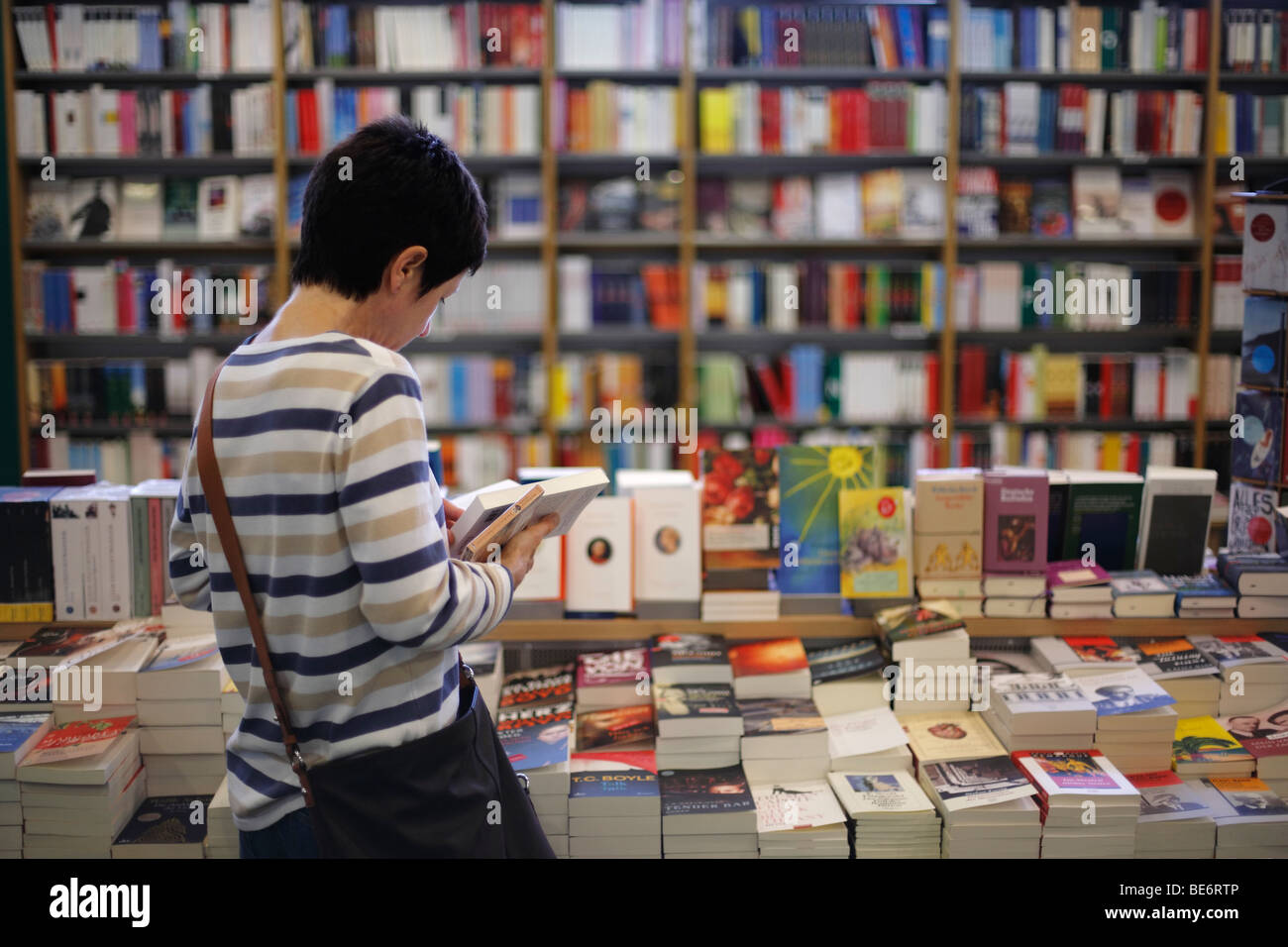 woman reading in books in a bookstore - Stock Image