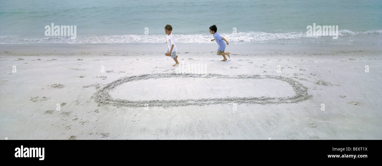 Boys running on beach, chasing each other around circle drawn in sand - Stock Image