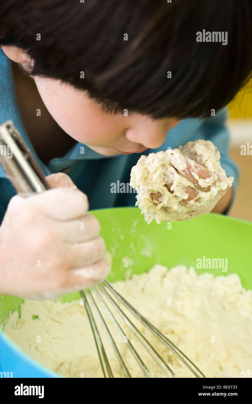 Little boy leaning over mixing bowl, smelling handful of dough - Stock Image