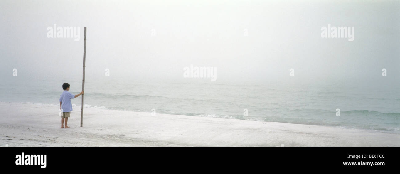 Boy on beach near water's edge holding up long section of bamboo - Stock Image