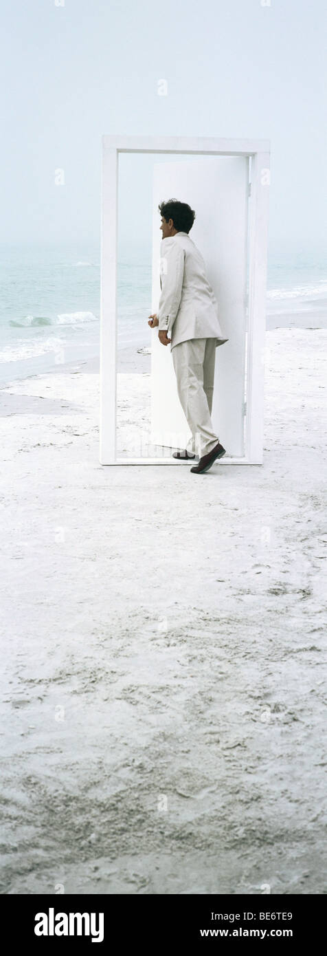 Man opening and entering door placed on beach - Stock Image