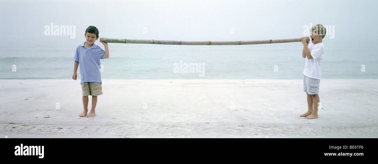 Two boys on beach talking to each other through length of bamboo - Stock Image