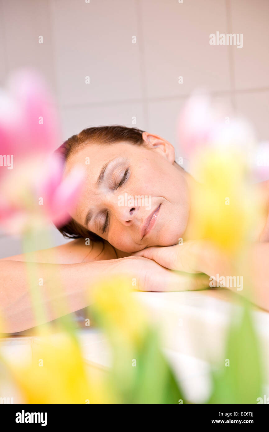 Woman relaxing in a bath tub - Stock Image