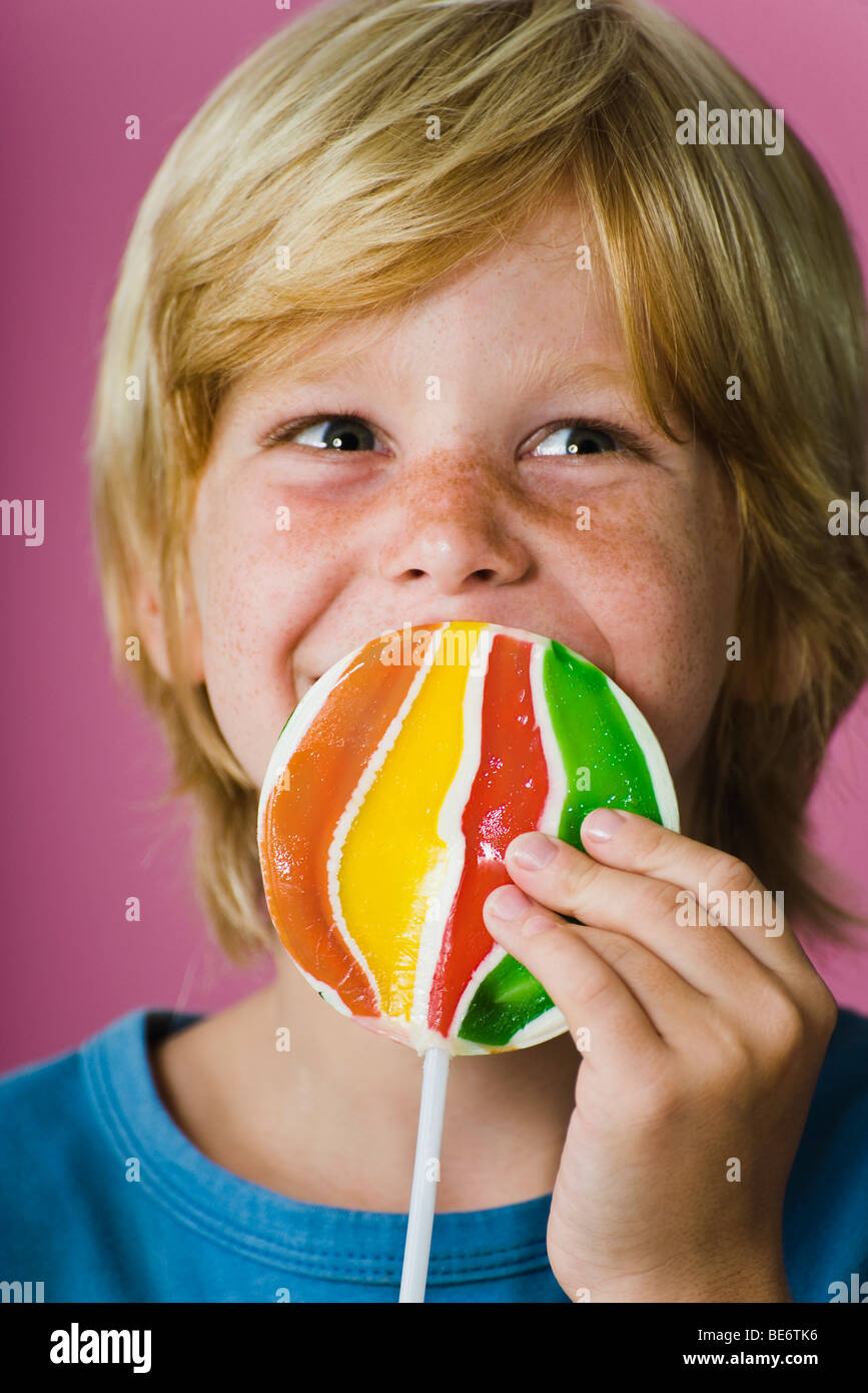 Boy holding large lollipop in front of face - Stock Image