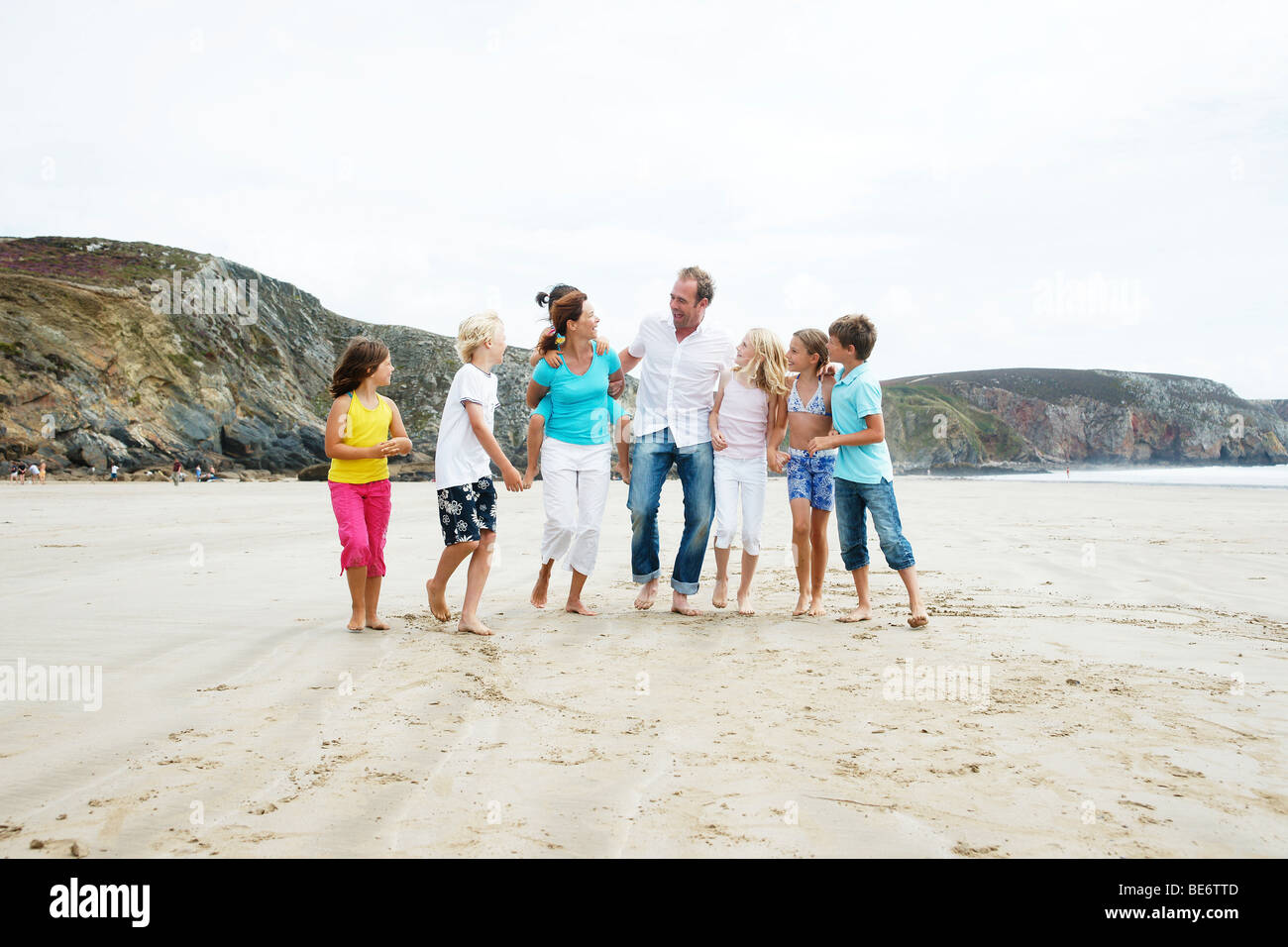 Woman, man, four girls and two boys walking along the beach, hand in hand, laughing, Bretagne, France, Europe - Stock Image