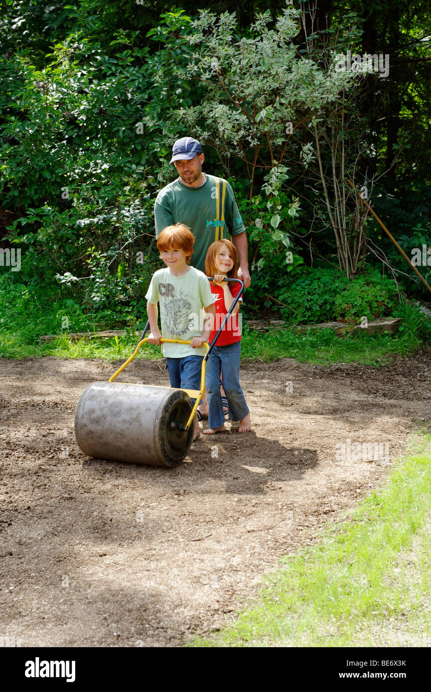 Family working in the garden, new grass, lawn, sod, turf, garden roller, roll, - Stock Image