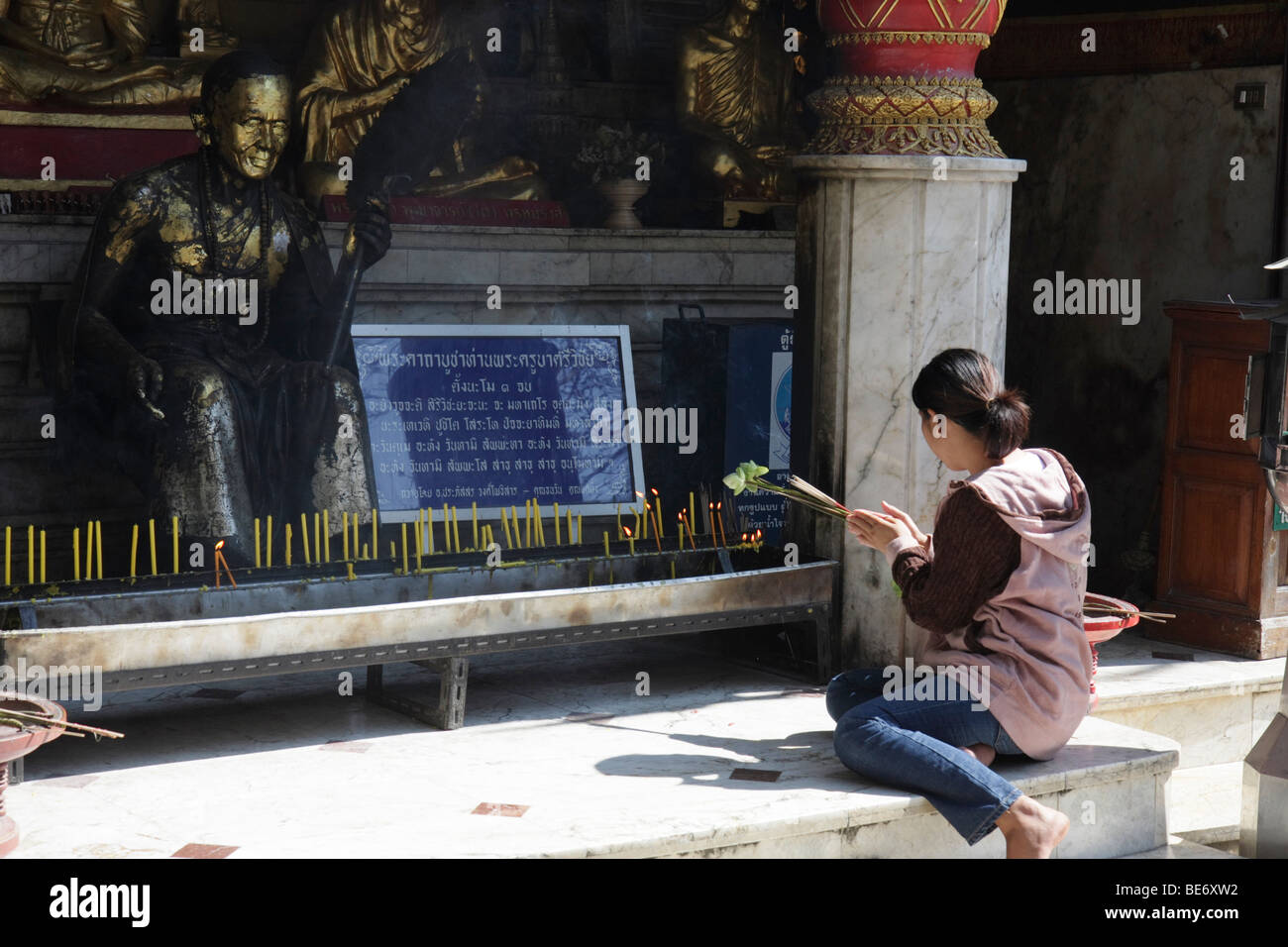 Buddhist praying with wooden flowers and incense, temple Wat Phra That Doi Suthep in Chiang Mai, Northern Thailand, Stock Photo
