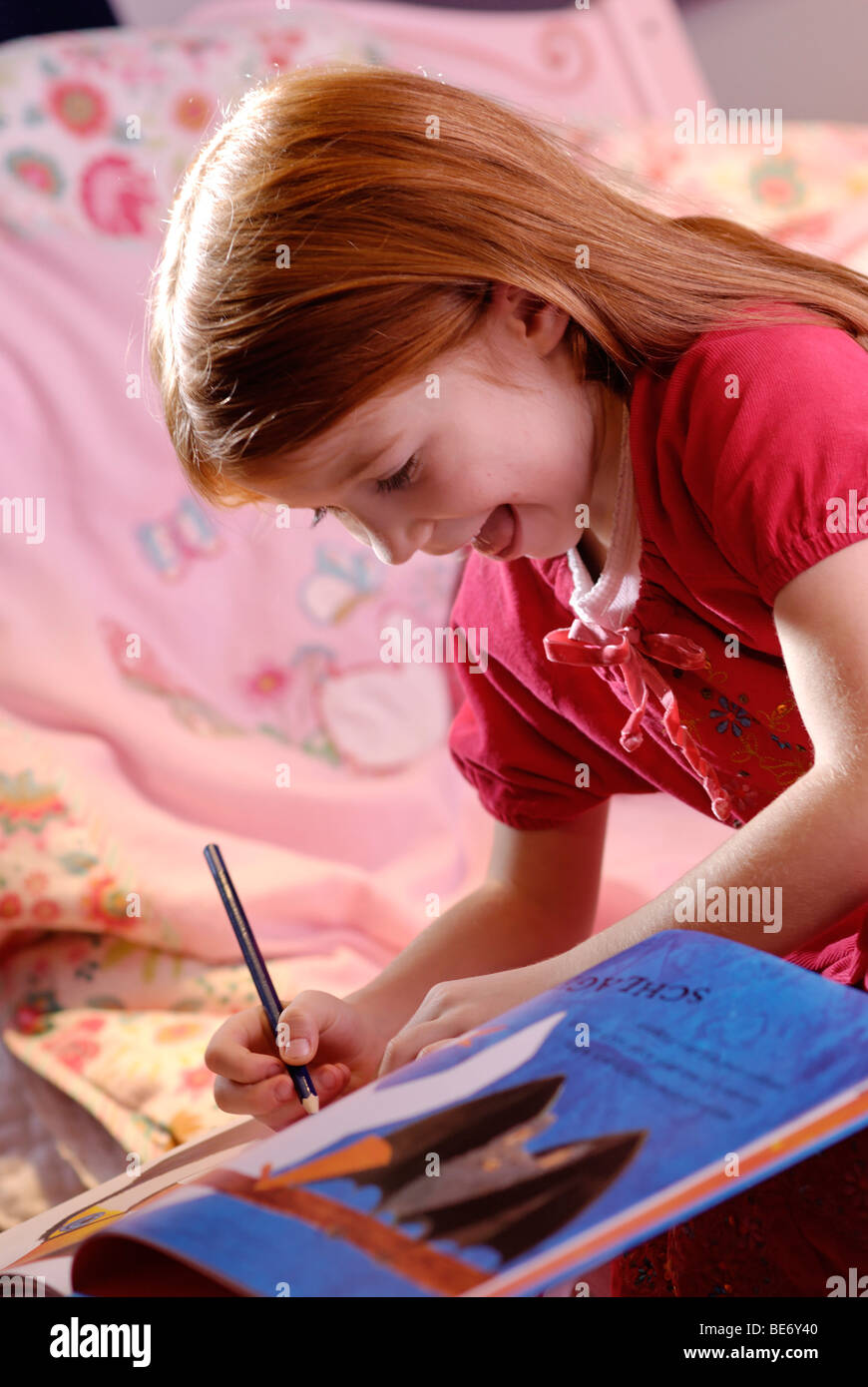 Little girl holding a pencil in her hand and writing or drawing - Stock Image