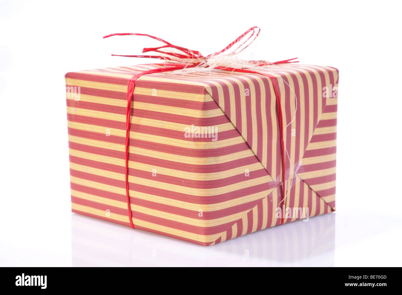 Present wrapped in striped wrapping paper and a bow - Stock Image
