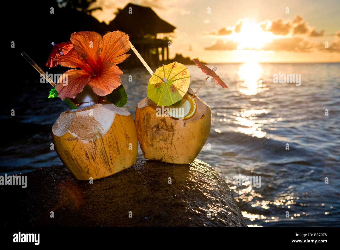 Two coconuts with cocktails and decorations on a granite rock at sunset, Seychelles, Indian Ocean, Africa - Stock Image