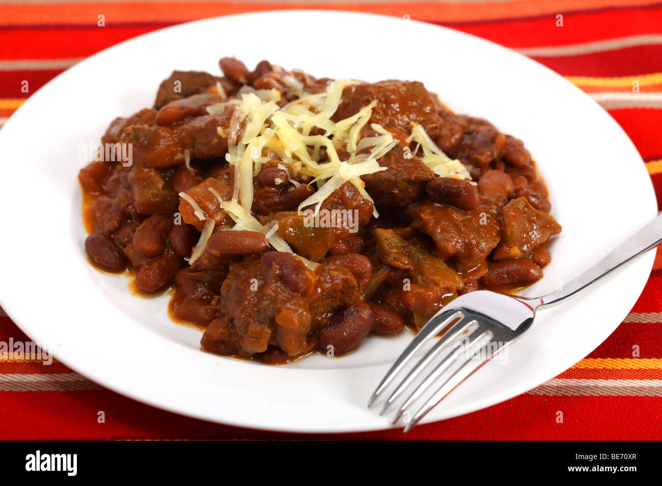 A plate of chili con carne made with red kidney beans and lumps of steak, topped with  cheddar cheese, with a fork Stock Photo