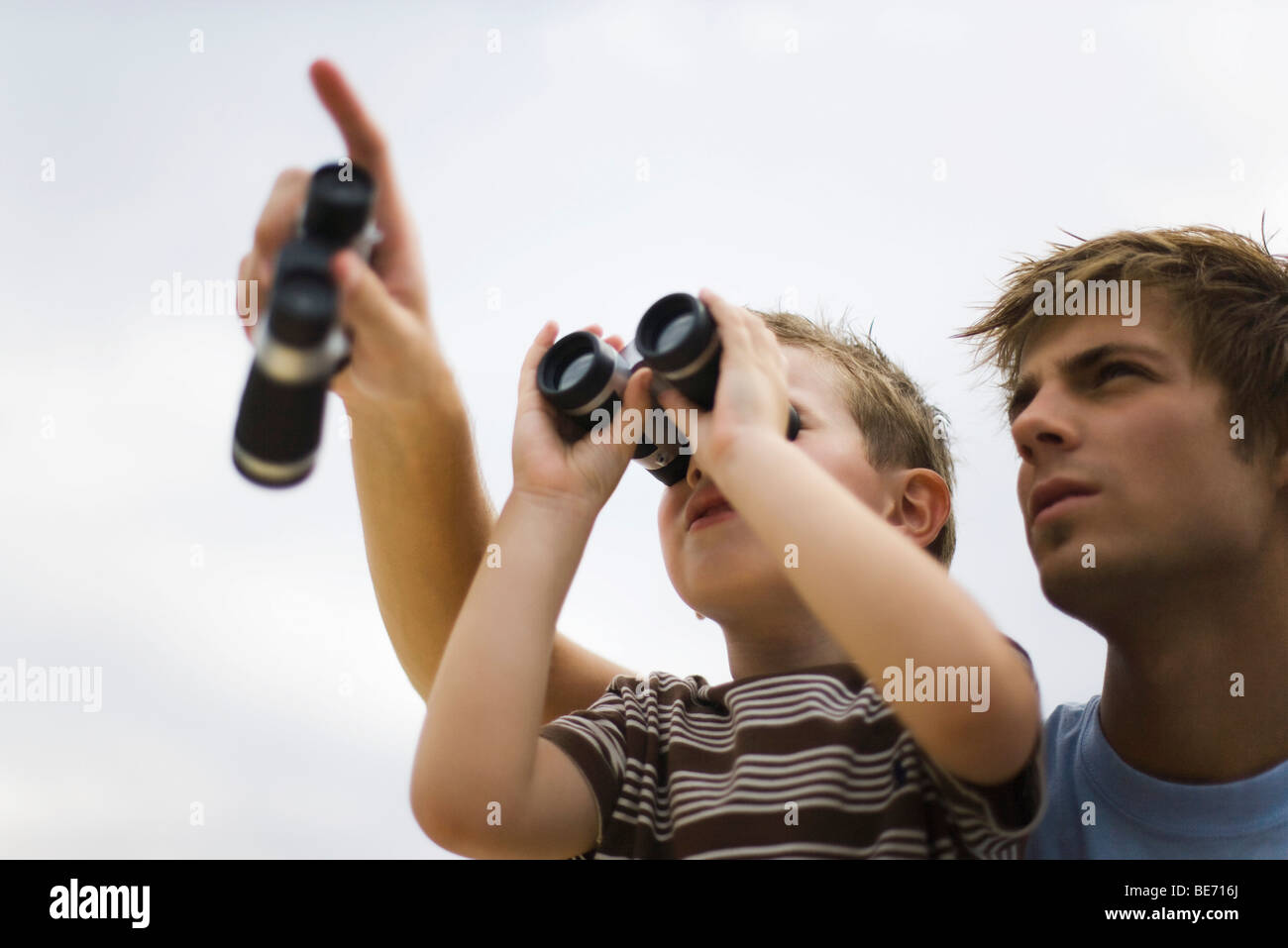Father and son using binoculars, man pointing skyward - Stock Image