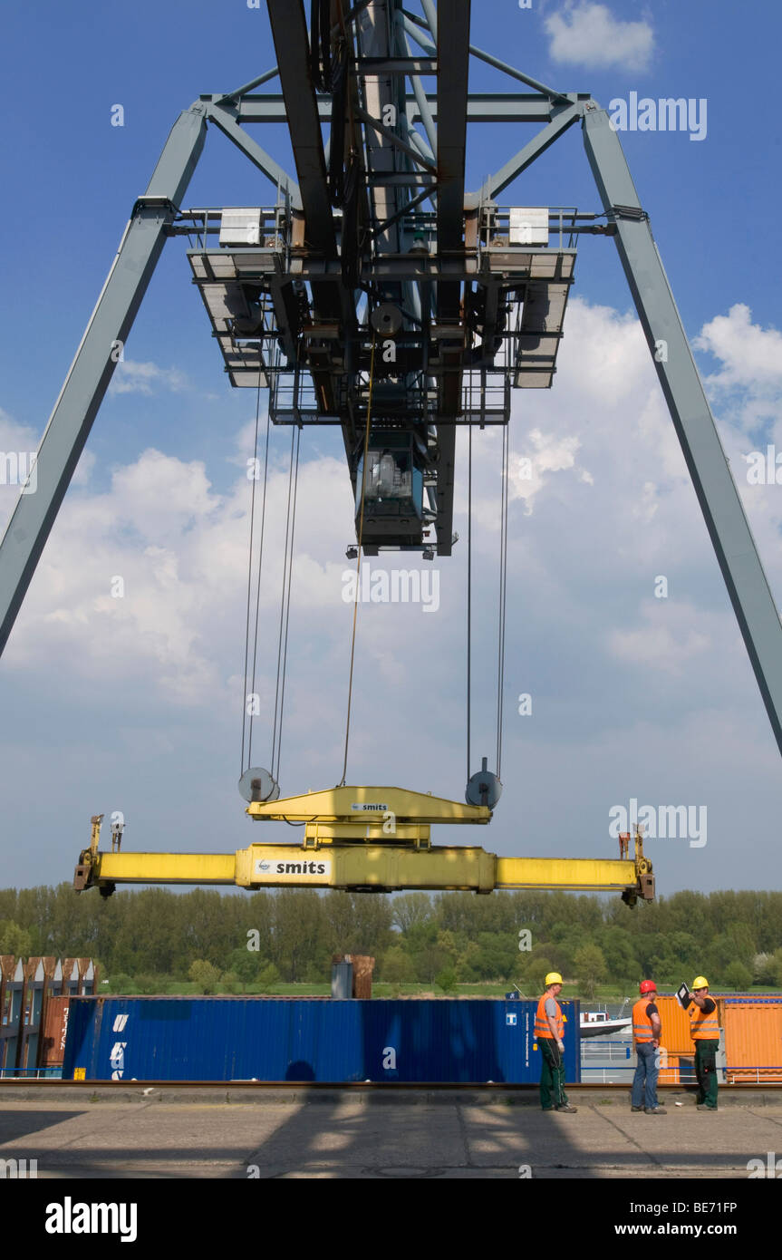 Container handling gantry crane over a barge, with workmen on the quay, port Bonn, North Rhine-Westphalia, Germany, - Stock Image