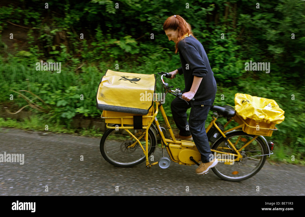 Mail carrier Annerose Schulze driving her company bicycle in her district for the Deutsche Post AG German Mail in - Stock Image