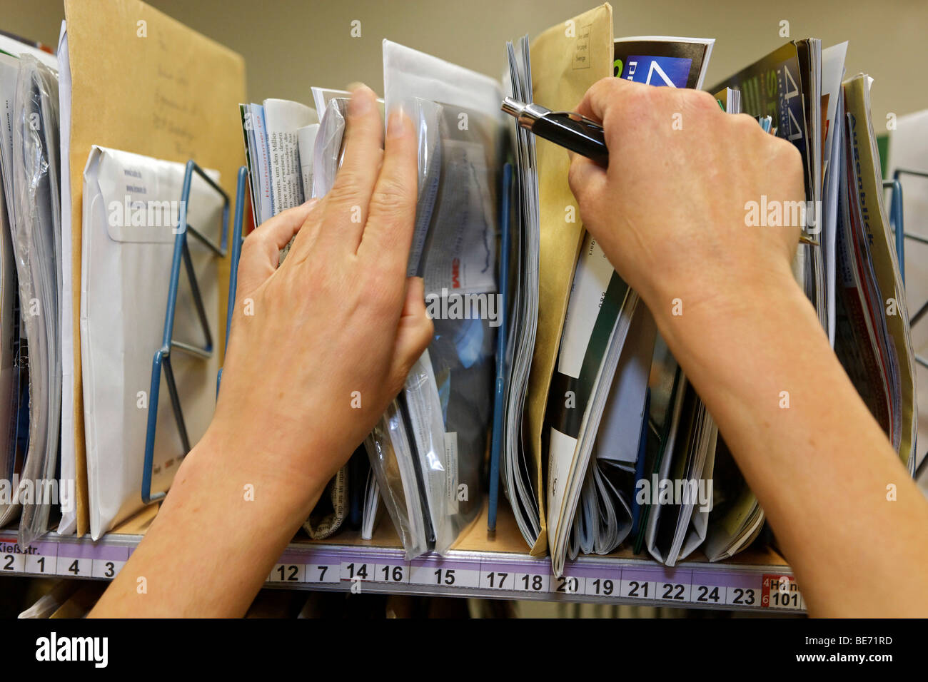 Mail carrier Annerose Schulze sorts her mail in the postal distribution center of the Deutsche Post AG German Mail - Stock Image