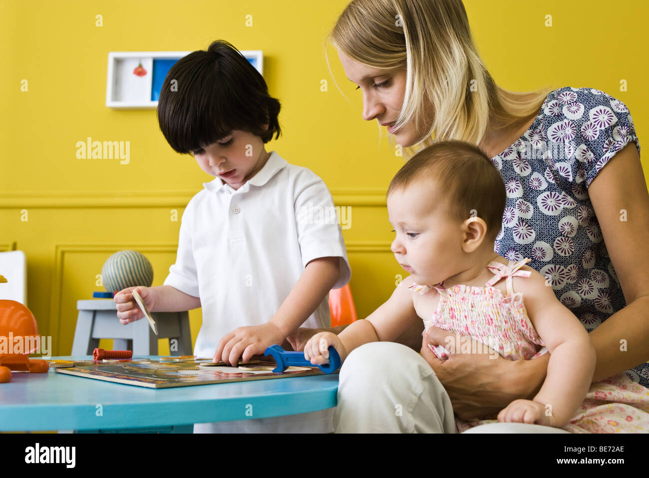 Little boy working jigsaw puzzle with mother and infant sister Stock Photo