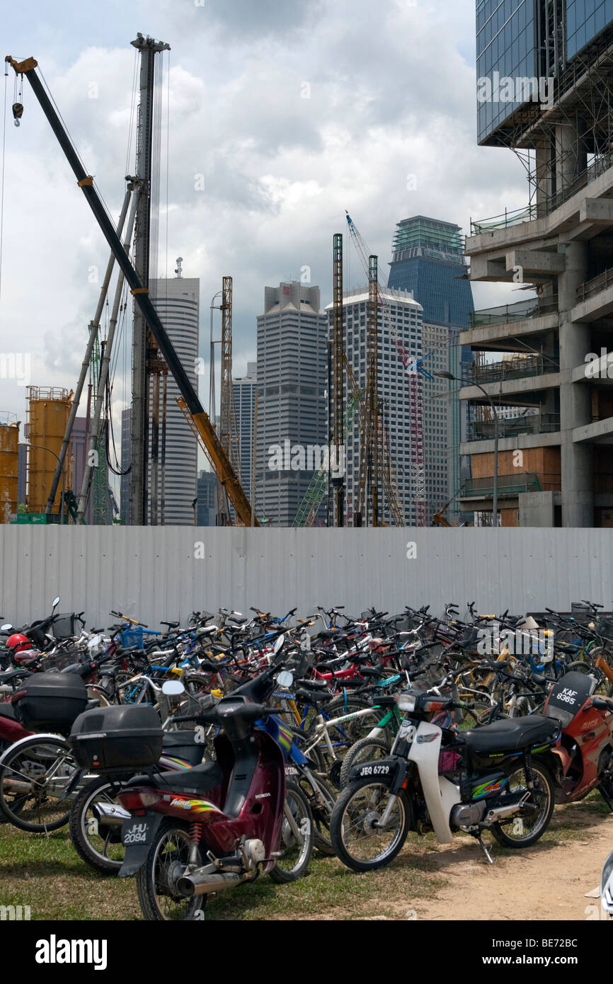 Bicycles and scooters in front of a construction site, building boom in Singapore, Asia - Stock Image