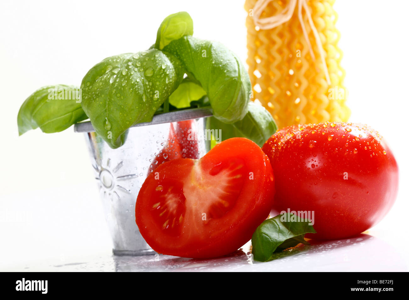 Tomatoes, one halved, with basil Stock Photo