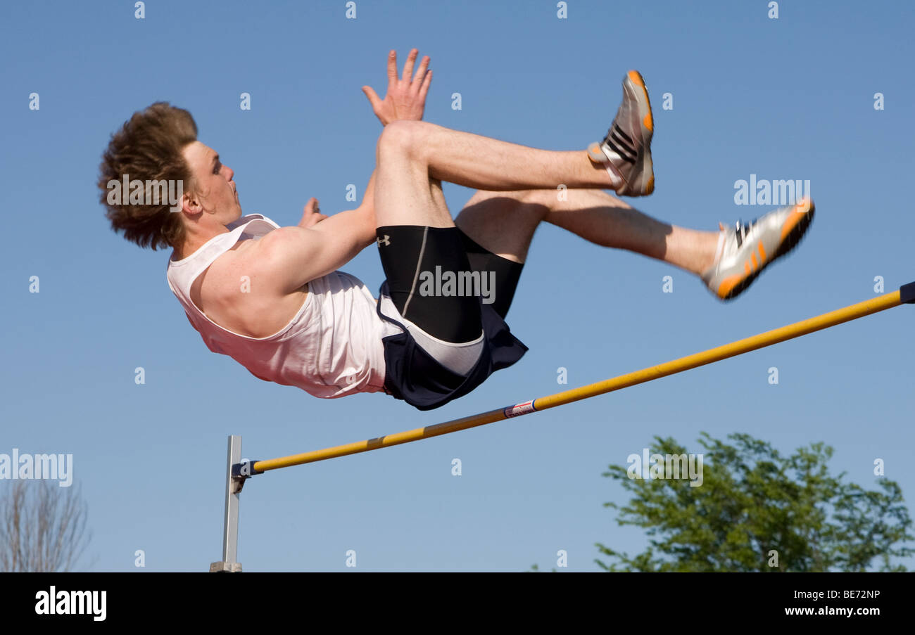 A high school boy wishes his body over the high jump bar. - Stock Image