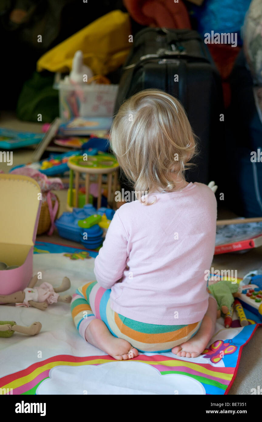 CHILD, TODDLER SURRONDED BY TOYS AND MESS. - Stock Image