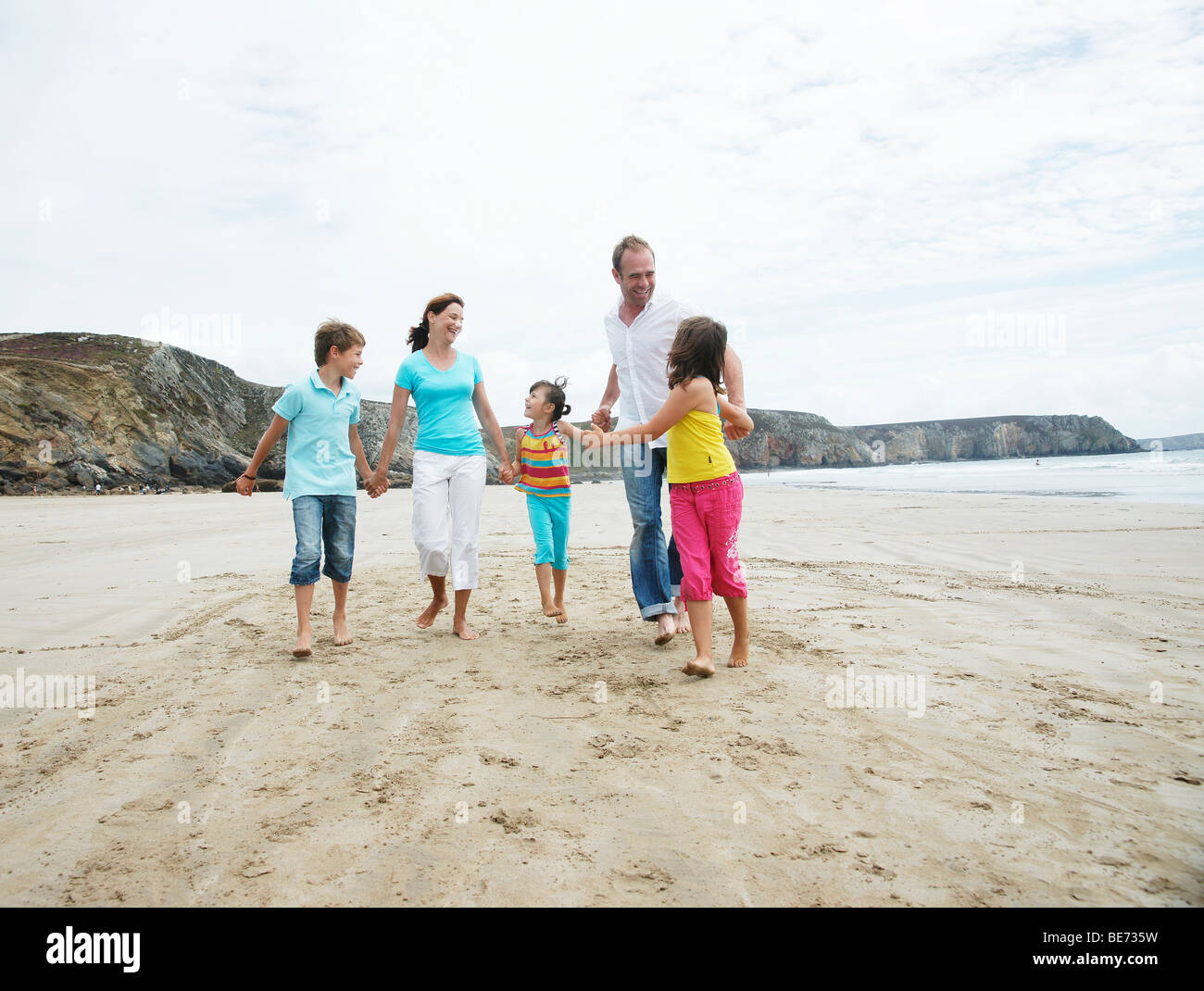 Woman, man, two girls and a boy walking along the beach, hand in hand, laughing, Bretagne, France, Europe - Stock Image