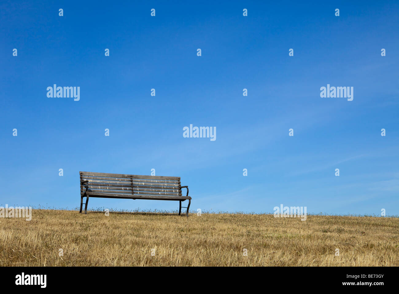 An empty park bench made of wood on dry grass is outlined against a blue sky with light clouds. - Stock Image