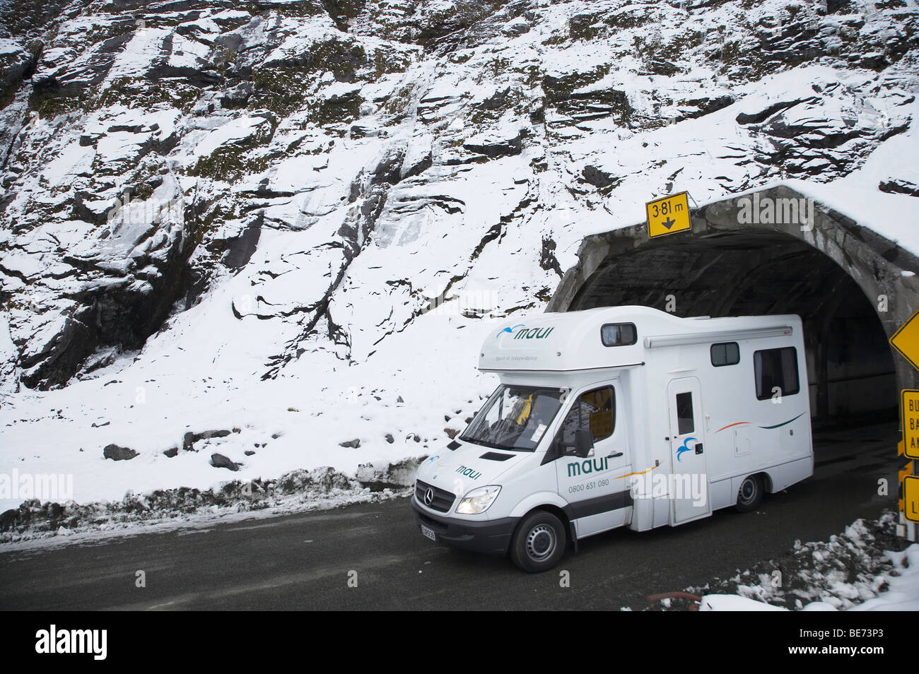 Campervan and Homer Tunnel in Winter, Milford Road, Fiordland National Park, South Island, New Zealand - Stock Image